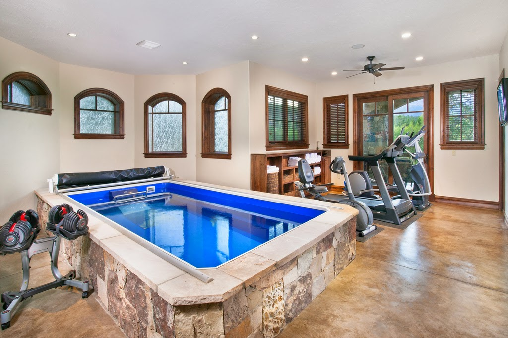 a partially in-ground Endless Pools swimming machine in a home gym