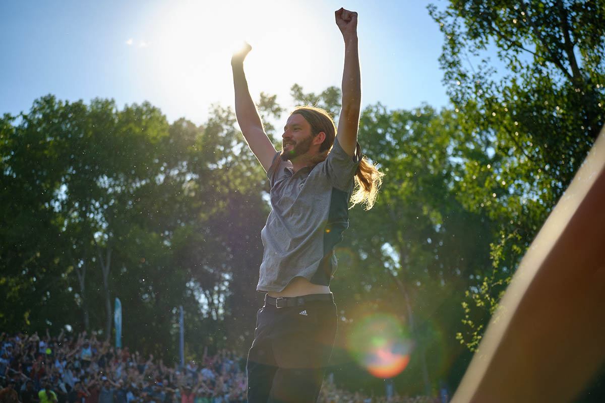 A man with his arms raised in the air in the sunshine
