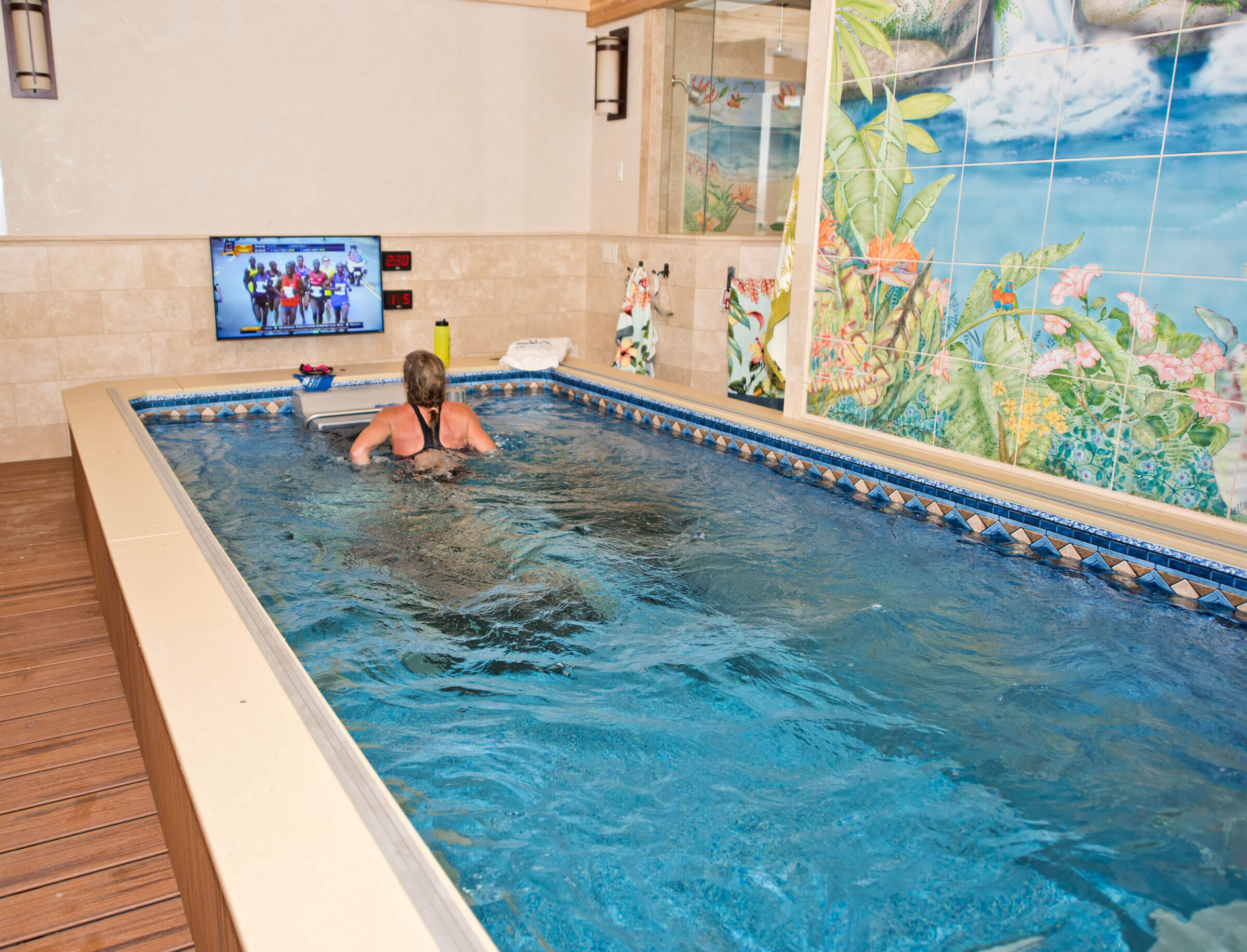 a woman runs on the Underwater Treadmill in her Performance Endless Pool while watching television
