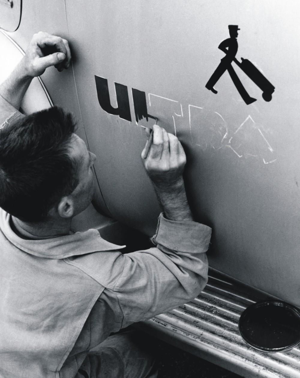 Foto em preto e branco de um homem pintando à mão o logo da Ultragaz na porta de um caminhão de distribuição de botijões.