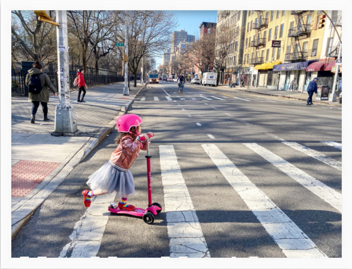 photo of little girl on scooter crossing street in white Irvine slim frame