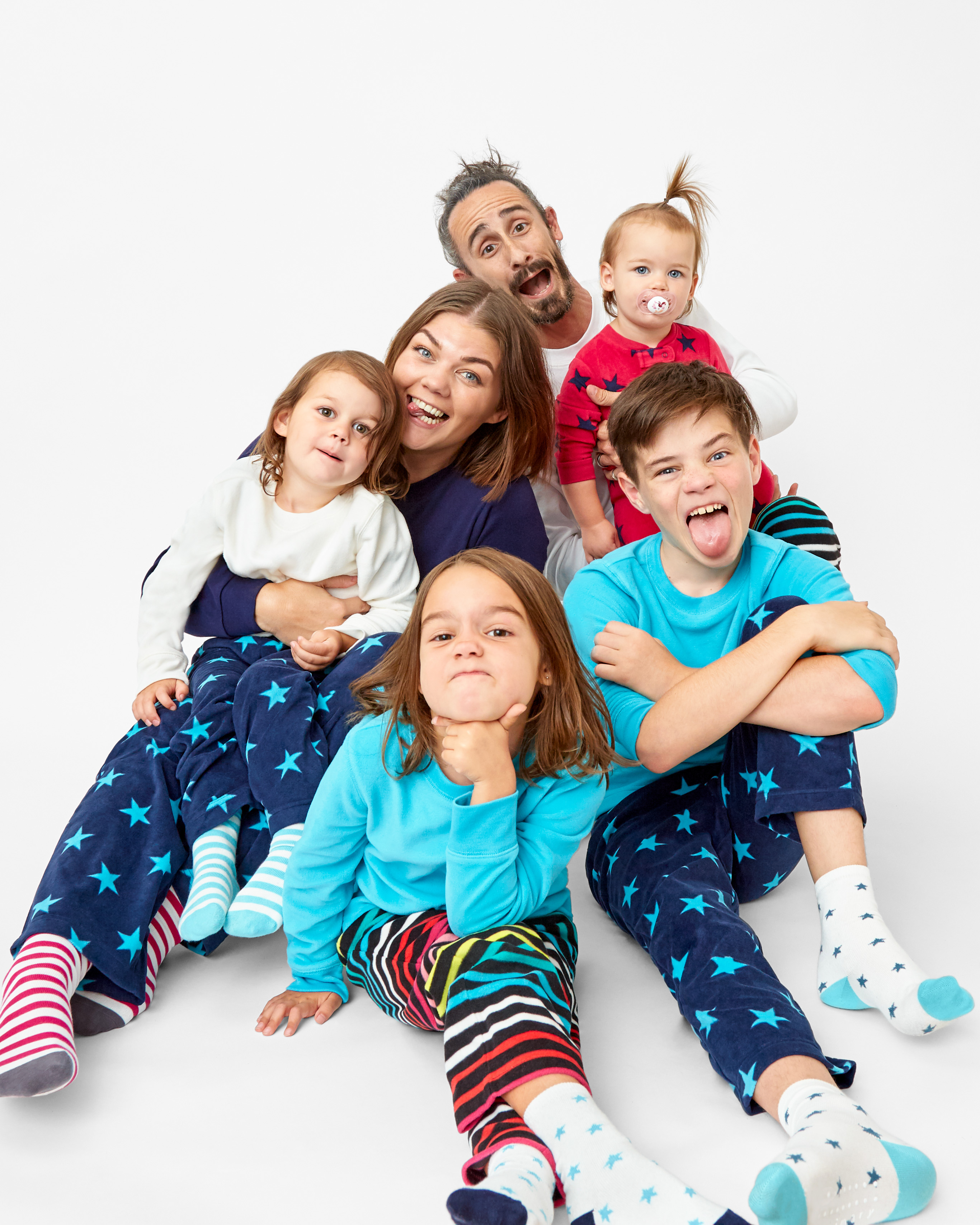 family sitting together wearing matching multicolored fleece pajamas