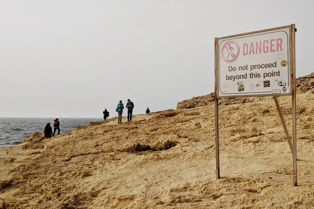 """People walking on a cliff behind a """"Danger"""" sign"""