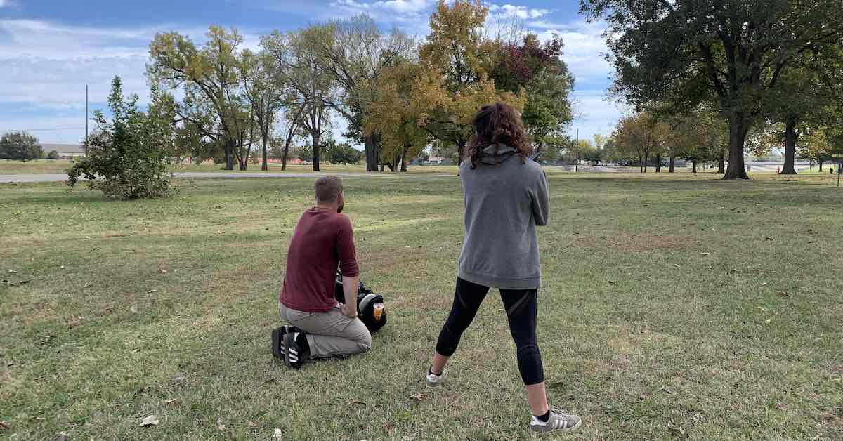 Kneeling man and standing woman on disc golf course as seen from behind