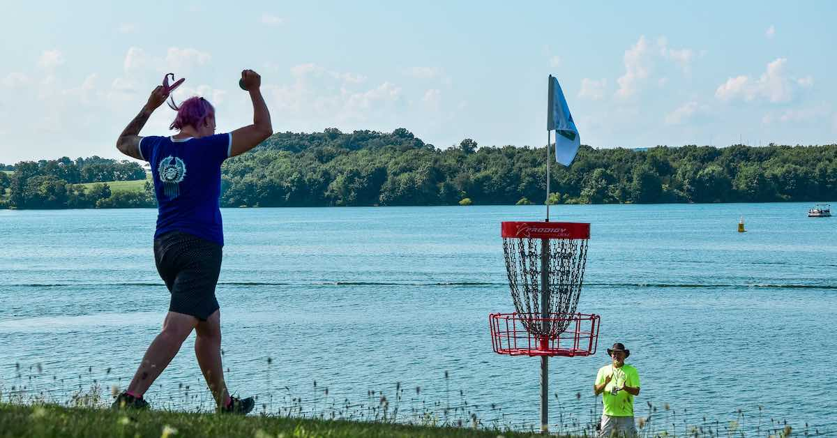 A woman walks toward a disc golf basket with fists raised in triumph