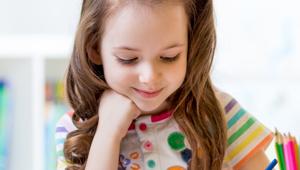 Foto de uma menina criança, loira, de cabeça mais baixa sorrindo como se estivesse olhando para algo apoiado na mesa. Vestida com uma blusa branca com vários detalhes coloridos nas cores do arco-íris.