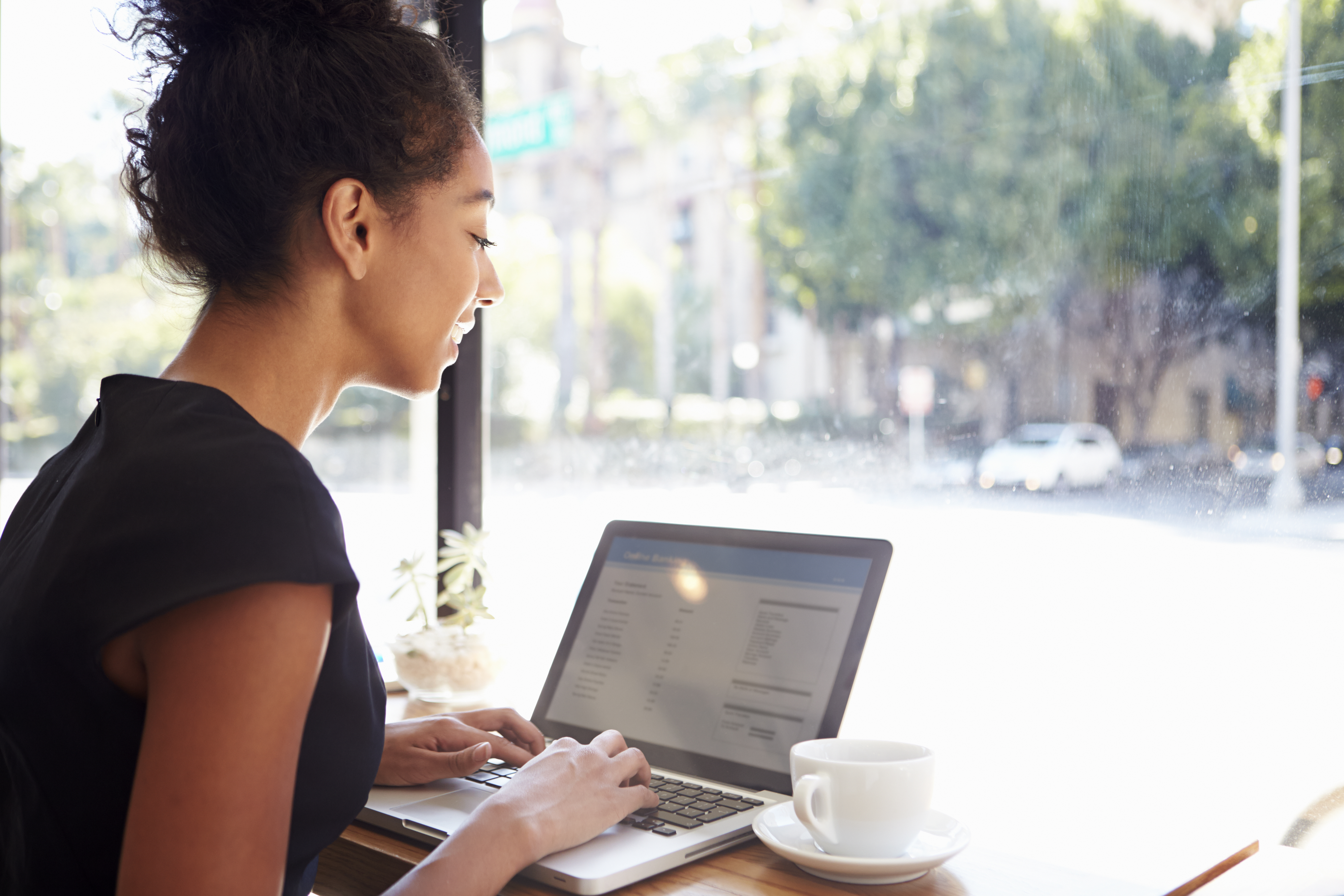 Woman working at a computer in a coffee shop