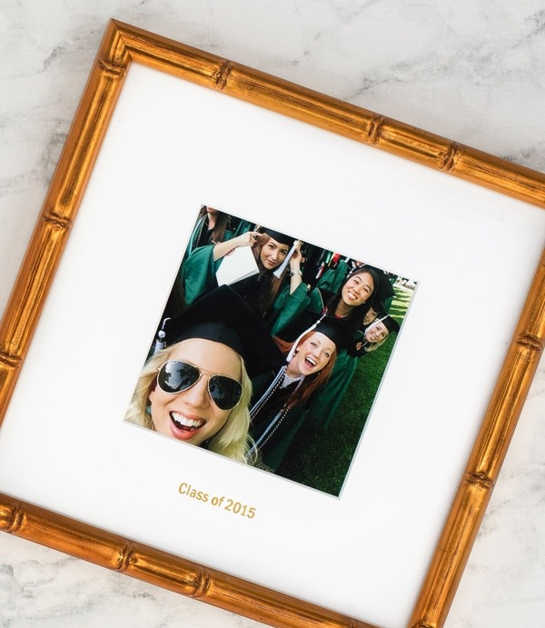 Framed selfie of girls graduating in caps in green and black gowns