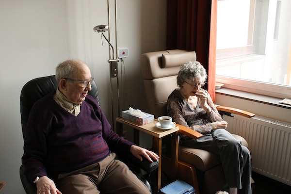 elderly man and senior aged woman seated side by side in nursing home common area by window