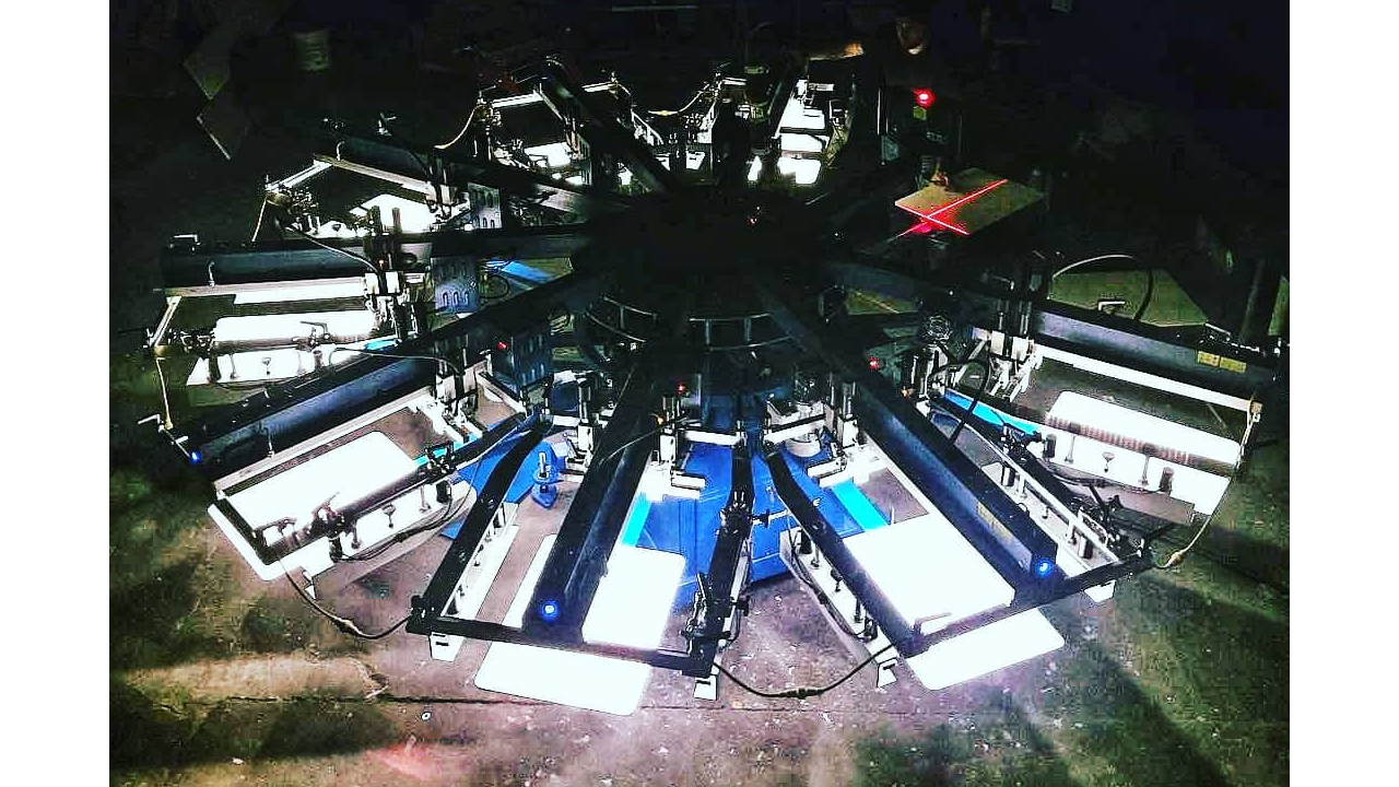 An automatic screen printing press from above with incredible lighting.