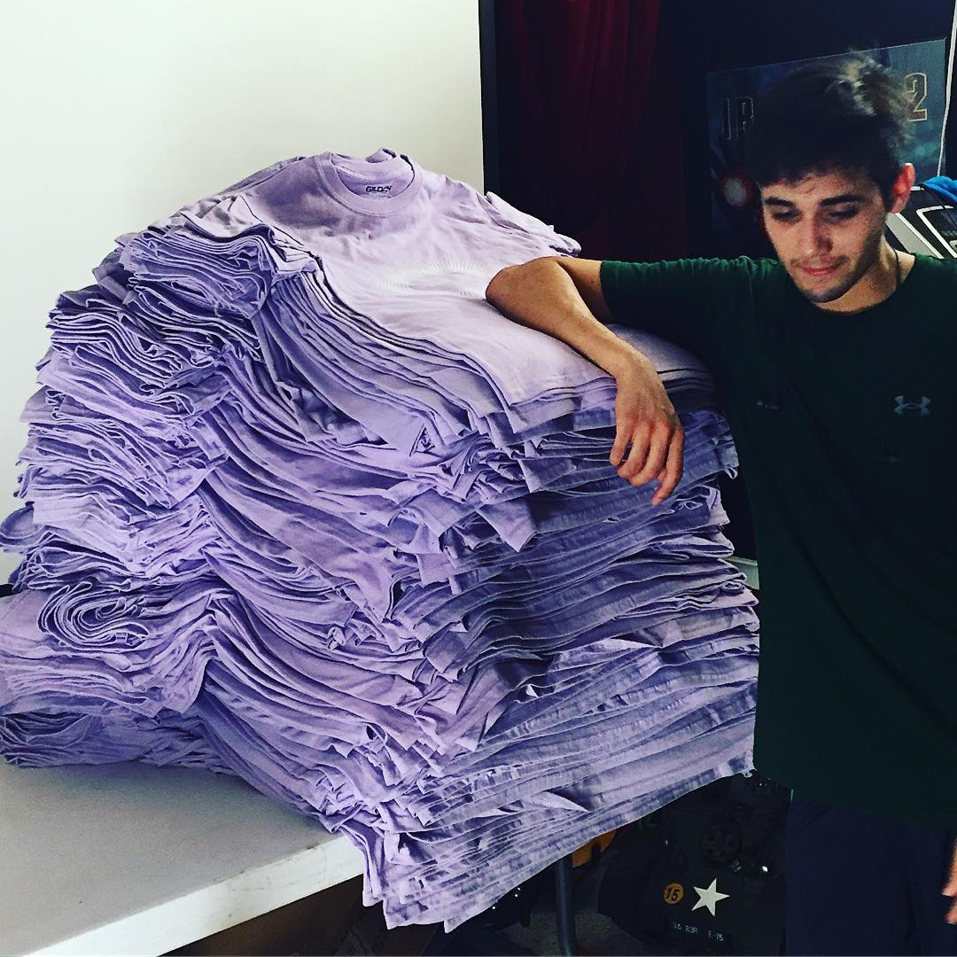 Success Print Shop's owner with a stack of t-shirts