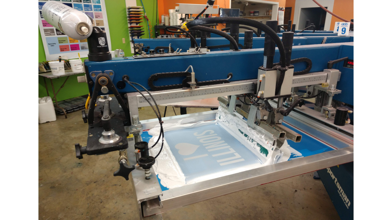 A screen printing machine's automatic squeegee. M&R Sportsman EX press at Campus Ink in Champaign, IL.