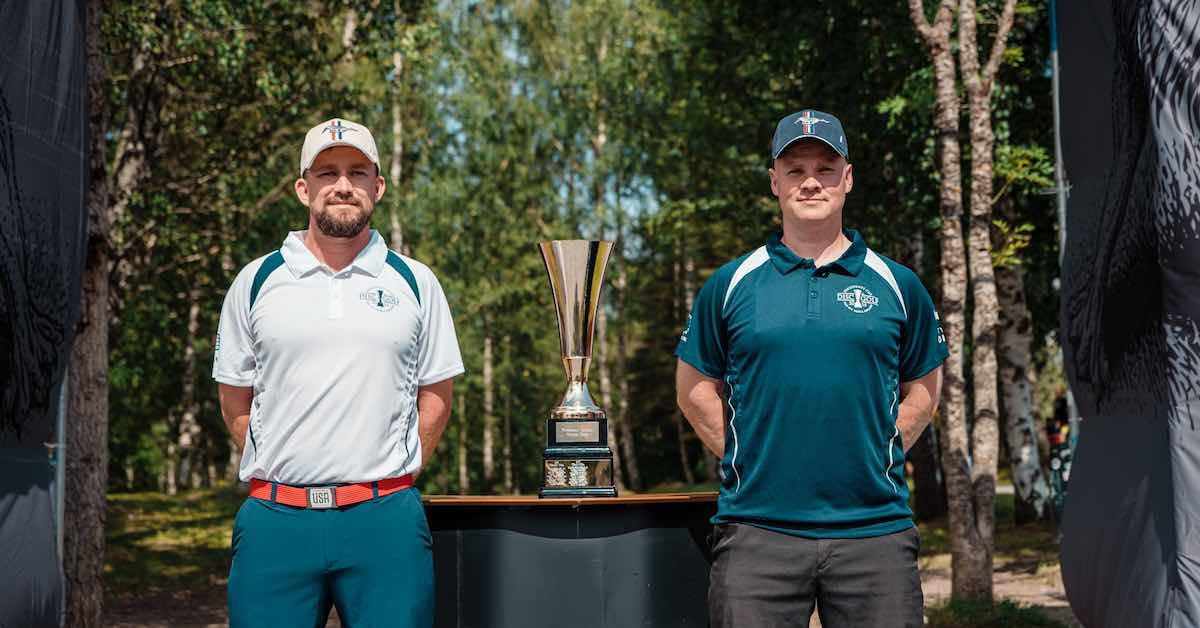 Two men, one in a white dry fit and hat and the other in bluish-green stand at attention on either side of a trophy