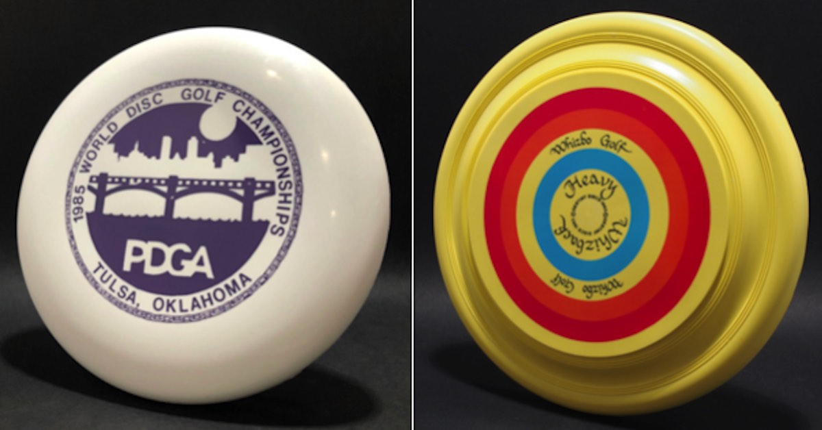 A white and blue Super Puppy from the 1985 PDGA Worlds and a yellow, red, and blue Whizback