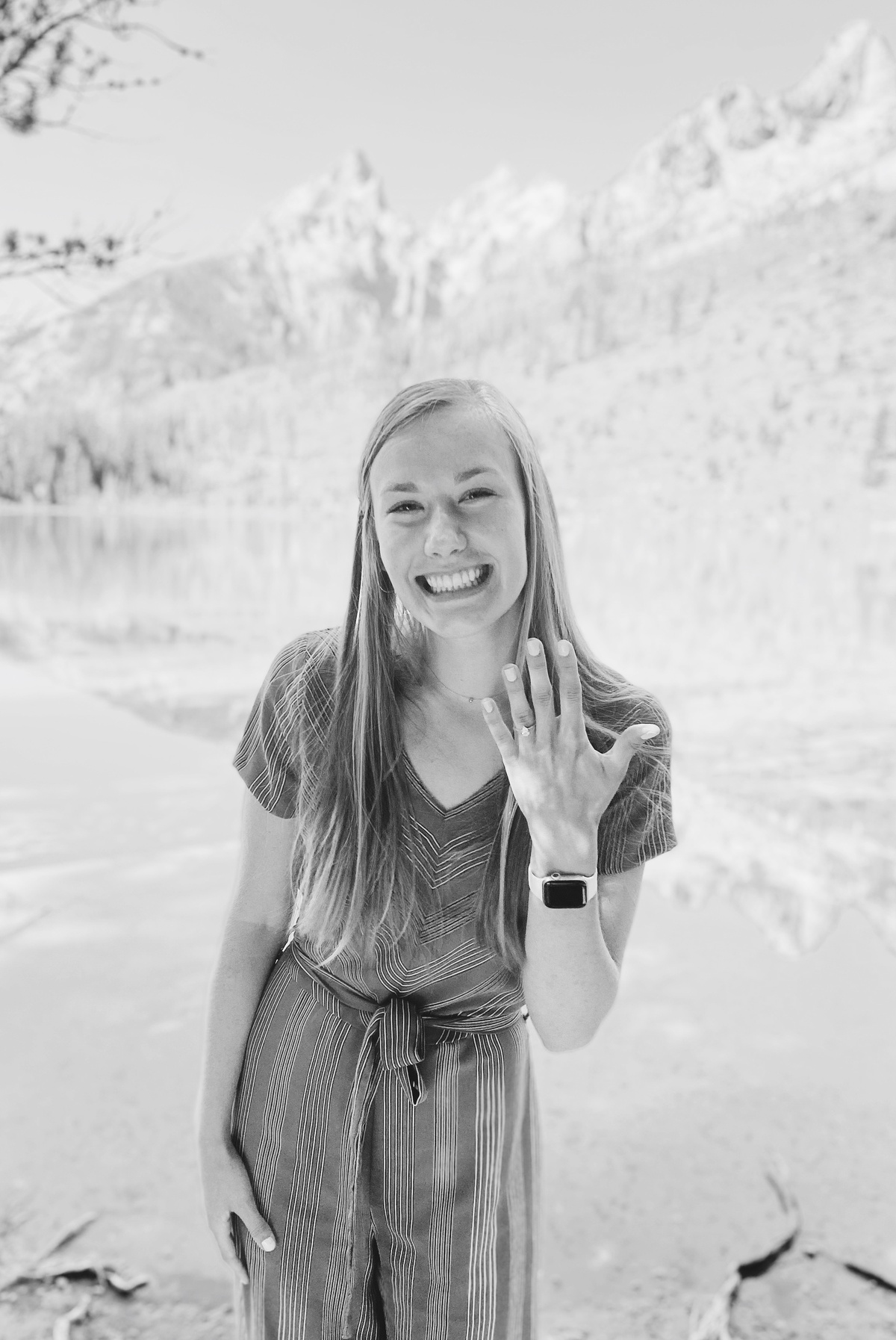 woman showing engagement ring in front of mountains