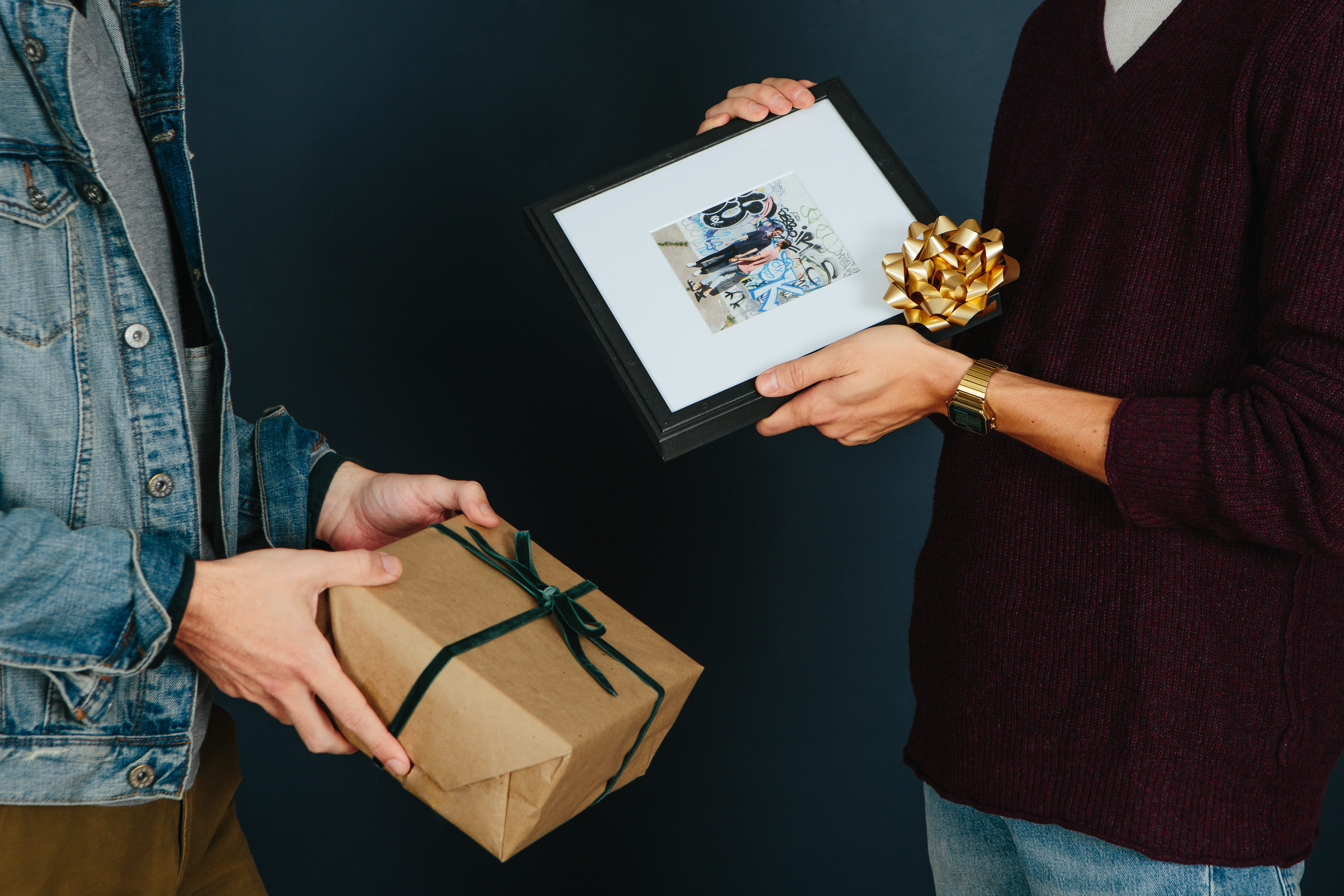 two men exchange gifts, a framed photo of them and a box wrapped in brown paper with a ribbon