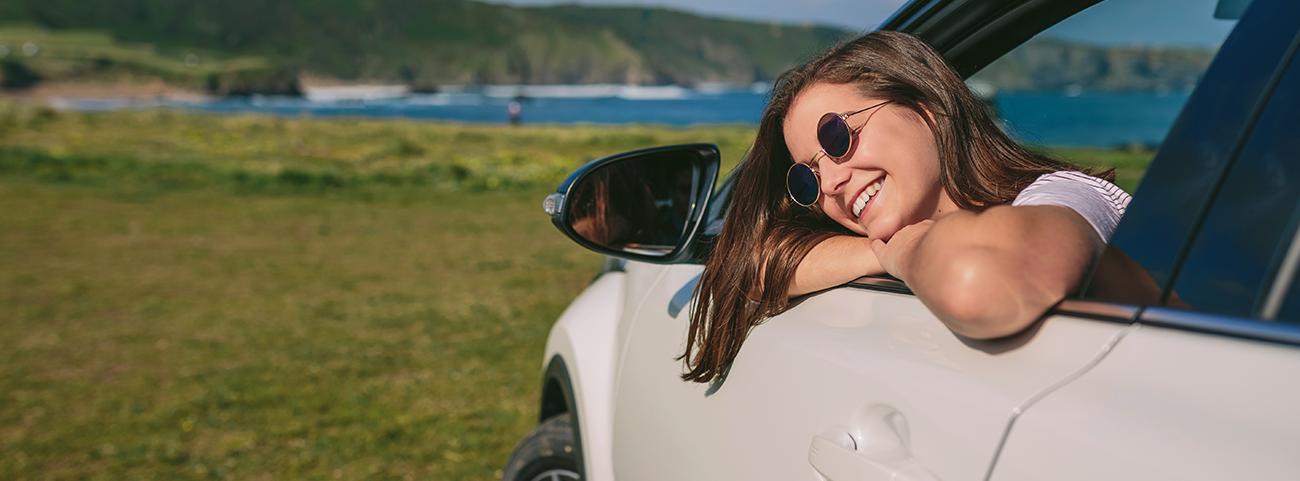 Mujer joven disfrutando de un viaje a bordo de un Seat León FR