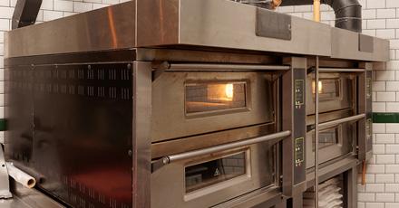 Foto de 4 fornos industriais em inox com suas portas fechadas mas interior iluminados.