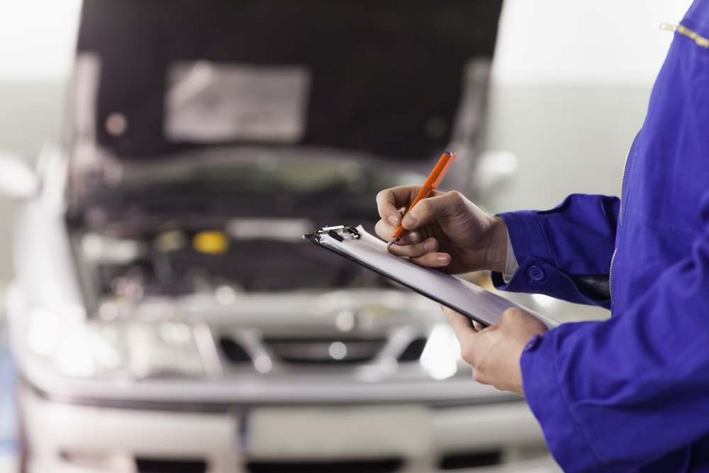 mechanic with clipboard checking car at garage