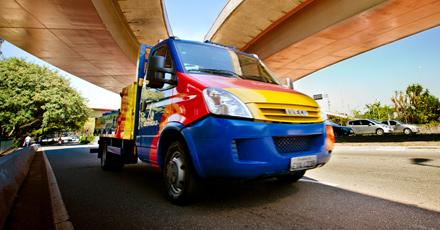Foto do caminhão da Ultragaz nas cores azul, vermelha e amarela passando em baixo de um viaduto. Ao fundo o céu está bem azul e tem algumas árvores também.