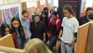 Foto de vários estudantes admirando uma exposição acompanhados de uma professora.