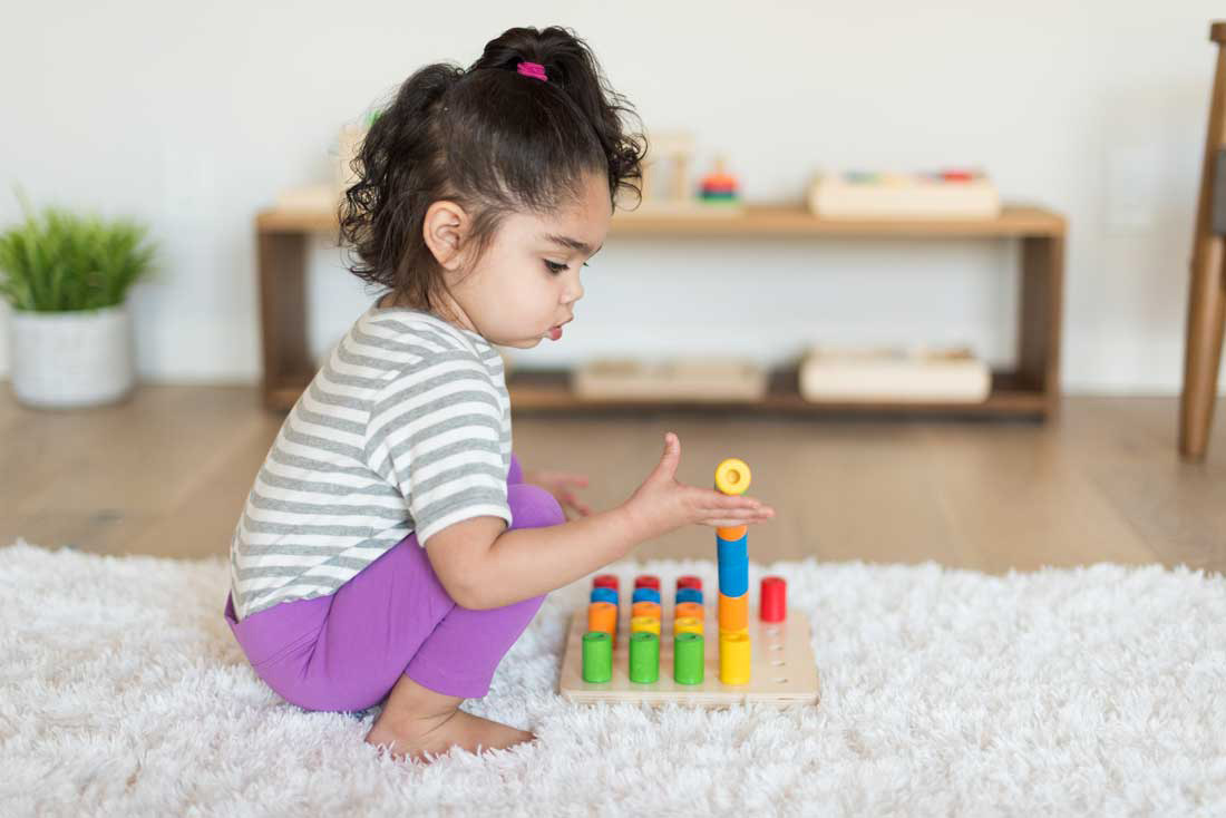 toddler wearing gray and purple playing with wooden stacking blocks