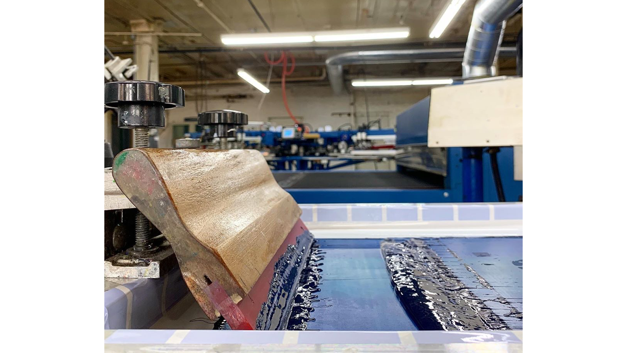 A squeegee sits on top of a screen for screen printing.