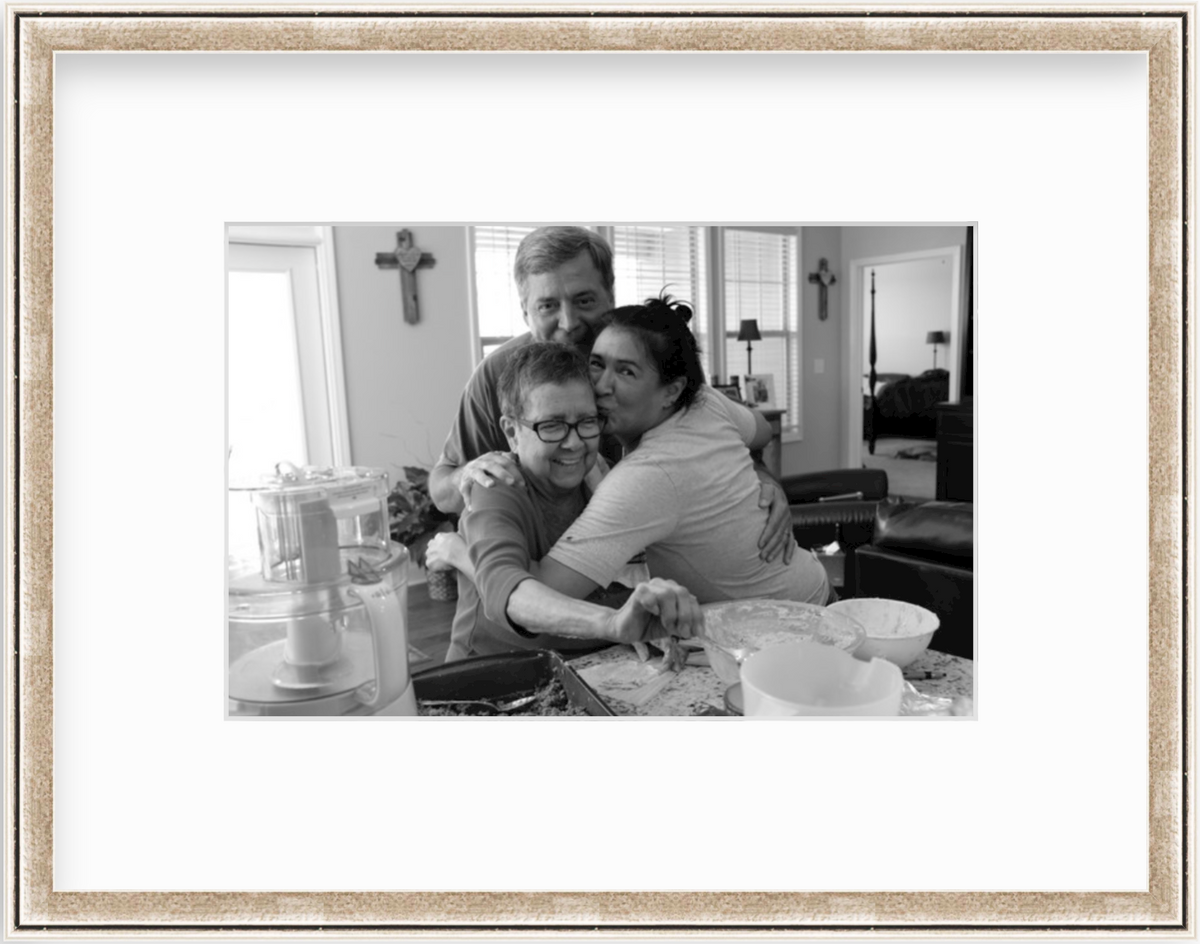 photo of family hugging with grandmother making tamales