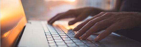 Imagem de duas mãos femininas digitando em um teclado de um notebook
