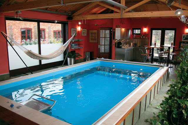 An Indoor Partially In Ground Endless Pools Swimming Machine With A Nearby Hammock