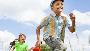 Foto de três crianças correndo em um dia muito ensolarado e com o céu cheio de nuvens.