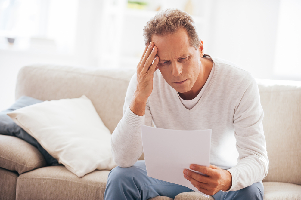 worried man holding a letter