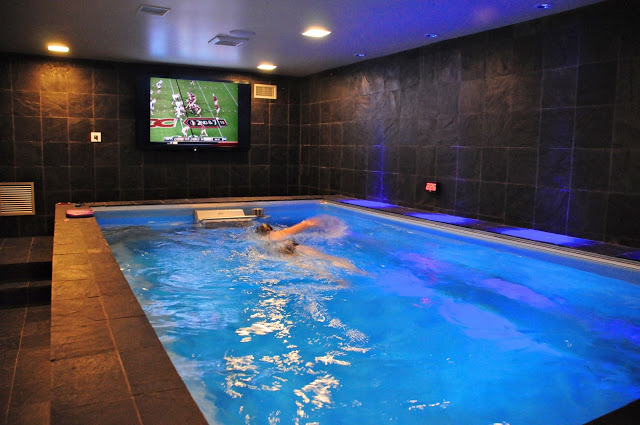 an indoor Endless Pools swimming machine in a black-tiled basement man cave