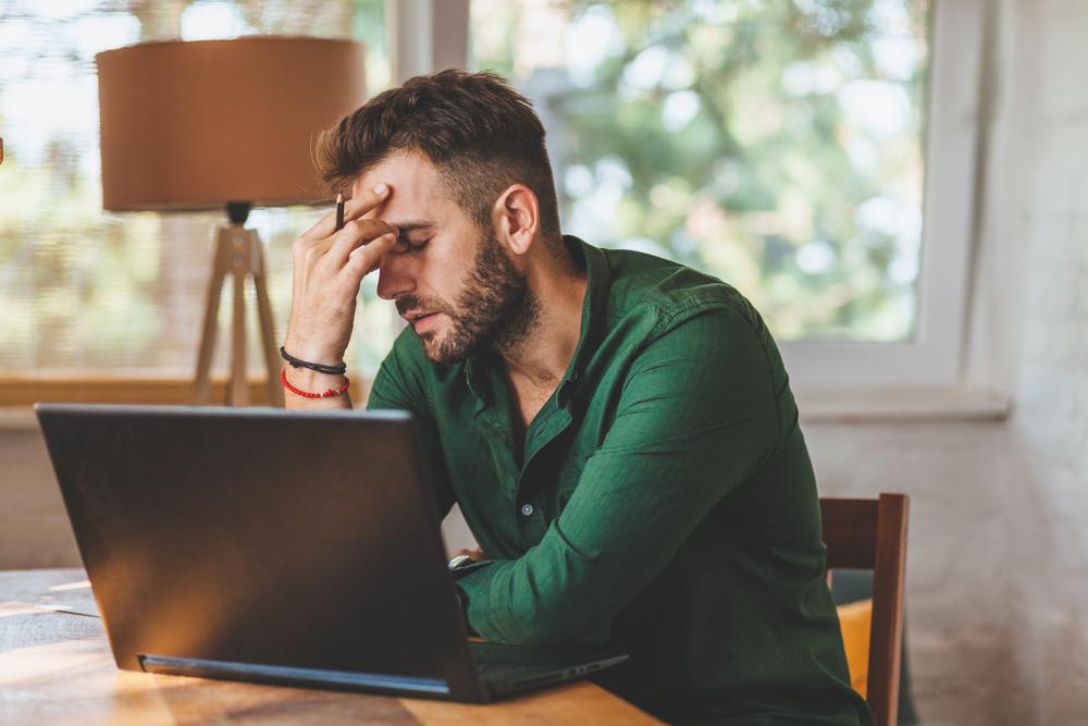 stressed man on laptop
