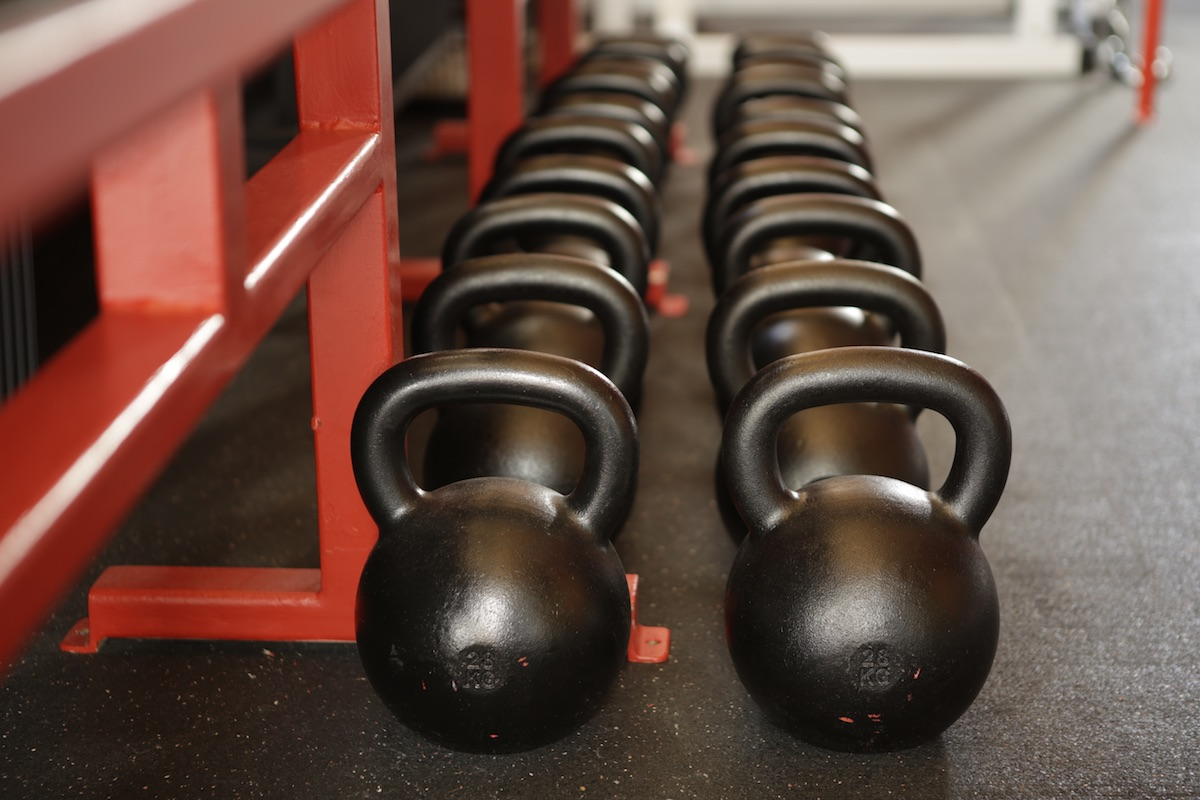 A row of kettlebells at a gym.