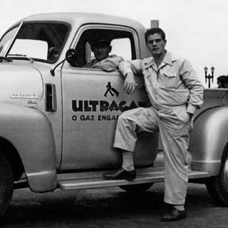 Foto em preto e branco tirada em 1937 do fundador Ernesto Igel vestindo um macacão apoiado em um caminhão da Ultragaz com logotipo estampado e um motorista dentro.