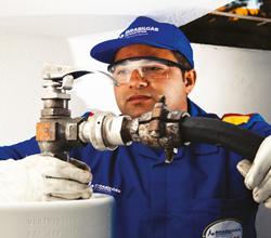 Funcionário da Brasilgás vestido com uniforme azul, equipamentos de segurança como óculos e boné, segurando válvula de abastecimento do cilindro de gás.