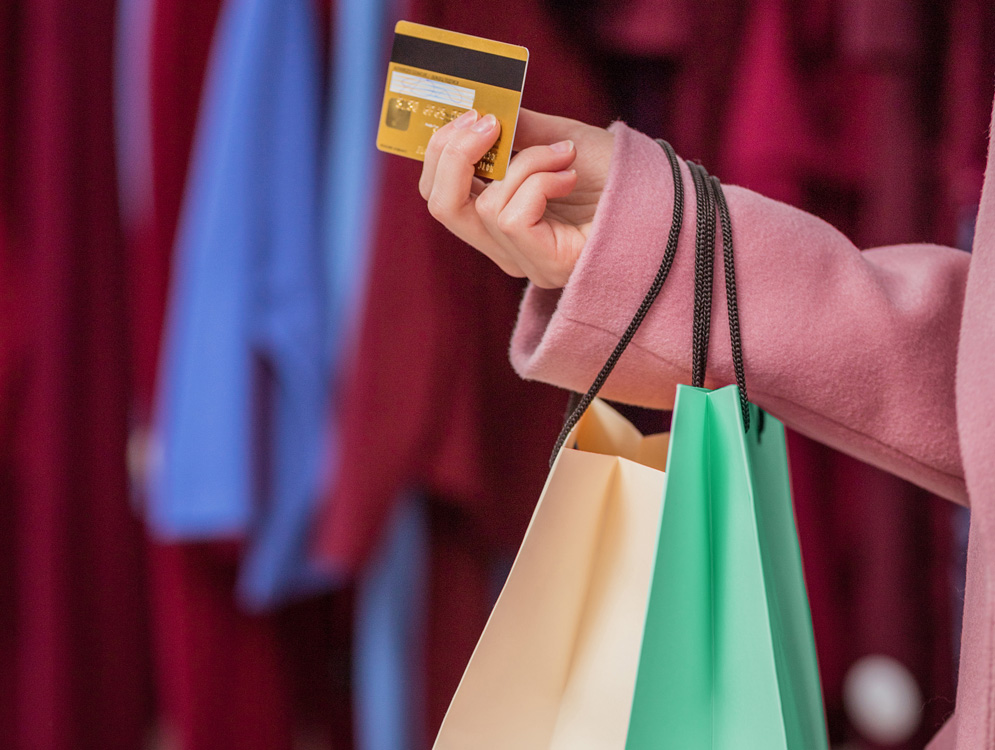 Person shopping with credit card, holding several bags full of purchased goods