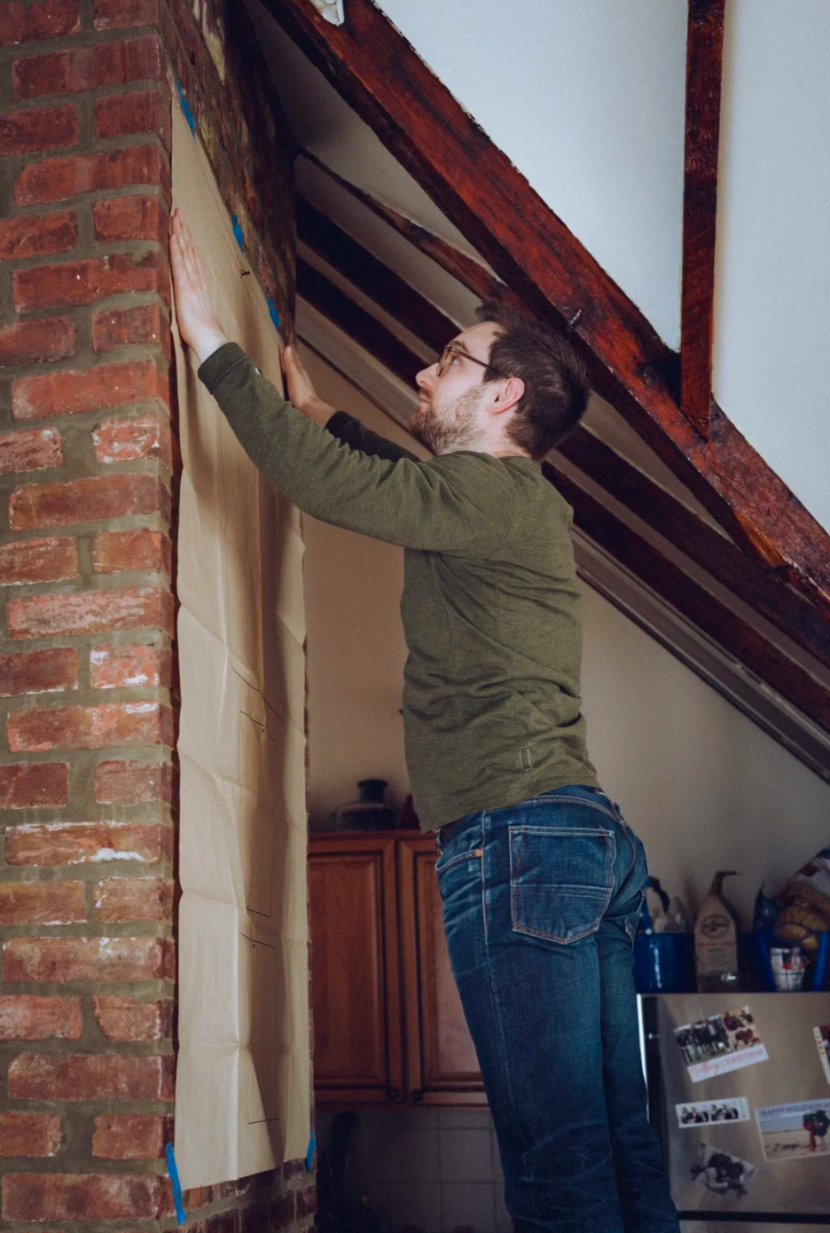 man using hanging guide on brick