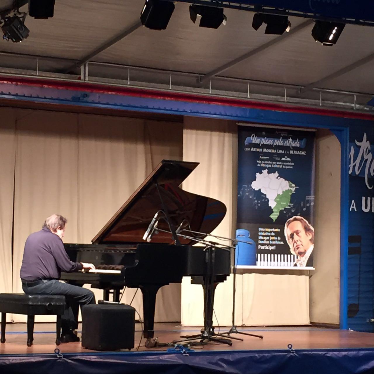 Foto de um pianista tocando seu instrumento em um palco