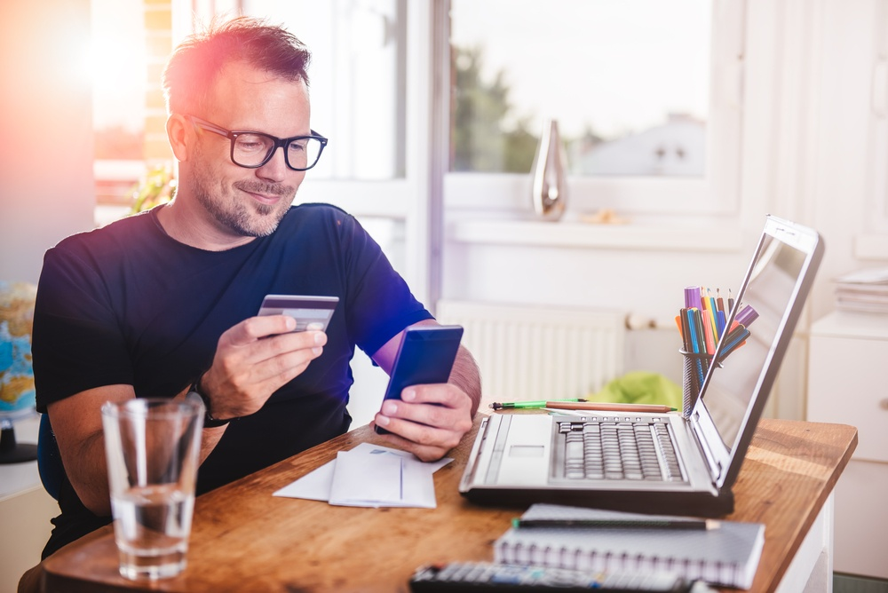 man checking card details on phone