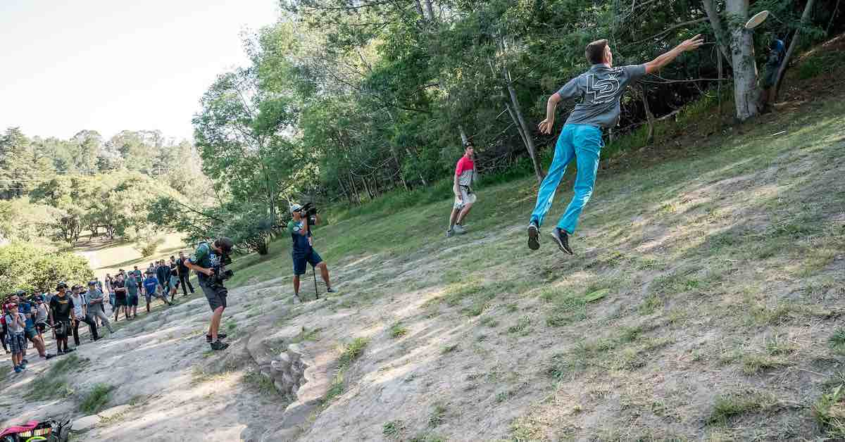 A crowd watches as a young male disc golfer jump putts up a steep hill