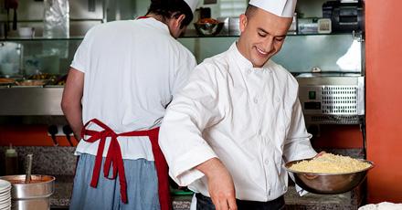 Foto de um cozinheiro segurando uma tigela com queijo ralado, sorridente, olhando para baixo. Ele e seu companheiro que está atrás e de costas, estão em uma cozinha trabalhando.