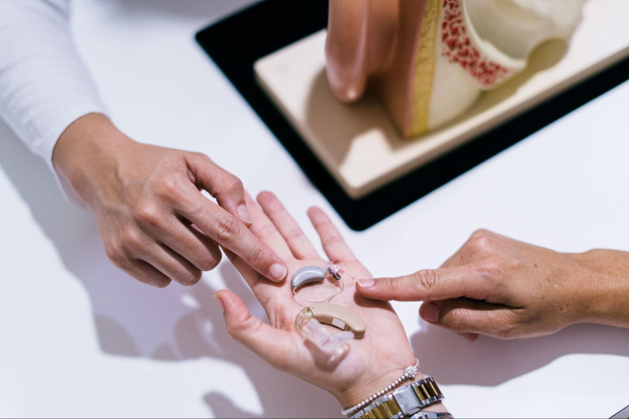 Hearing Care Solutions: hands pointing at a hearing aid