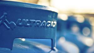 Foto da parte de cima de um botijão, onde segura, com o logo da Ultragaz estampado. O botijão é azul. O fundo da foto está desfocado.