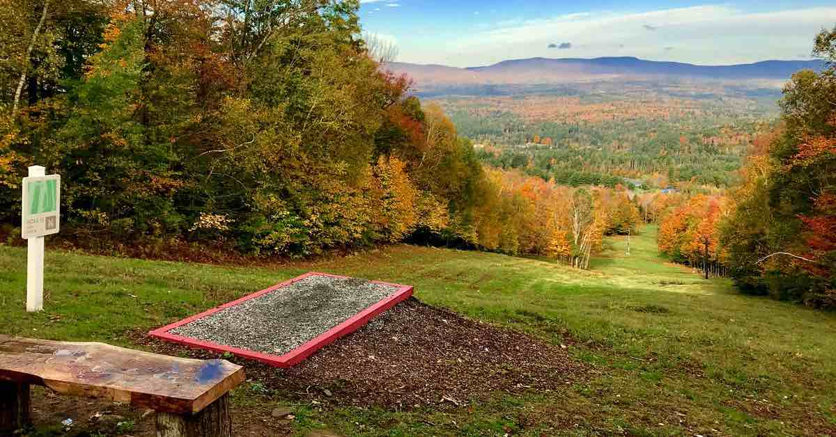 A disc golf tee pad at the top of a smooth, grassy slope with a view of trees in fall colors and mountains in the distance