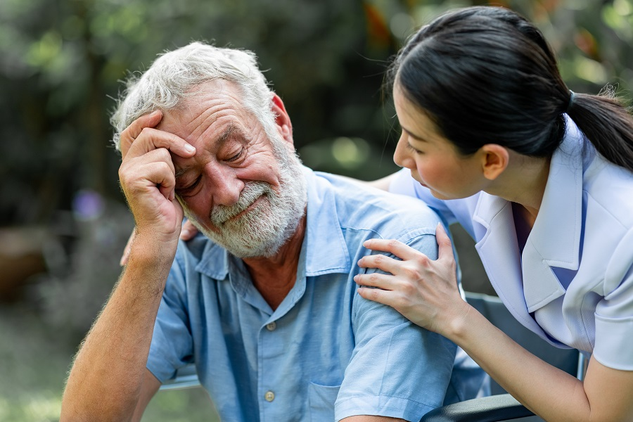 nurse at assisted living facility comforting elderly man with dementia