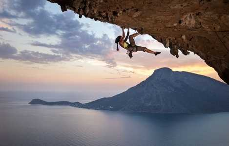 Person rock climbing with the sea,  a mountain peak, and sunset in the background