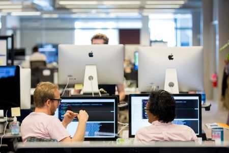 Office workers sit side by side in front of their computers while having a conversation