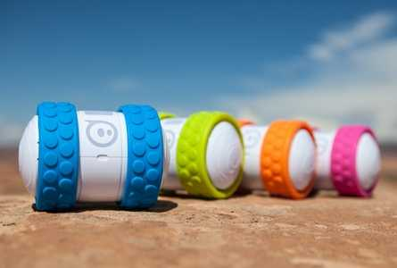 4 toy robots featuring 2 colorful tread wheels each lined up on the ground outside